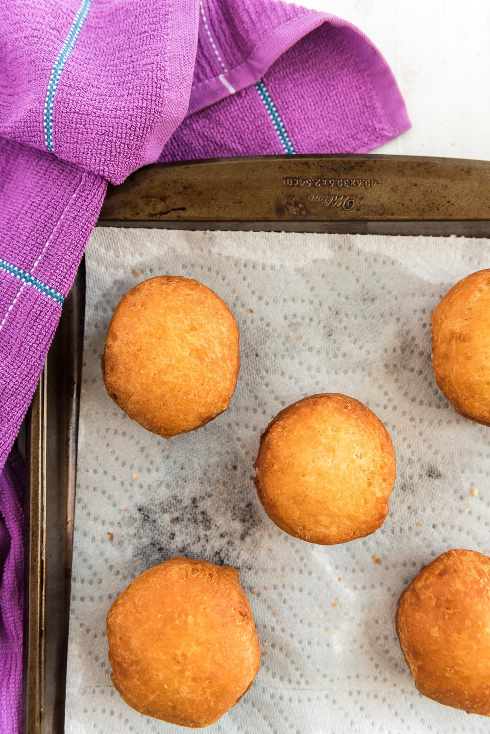 Fried donuts on a paper towel-lined baking sheet with purple napkin.