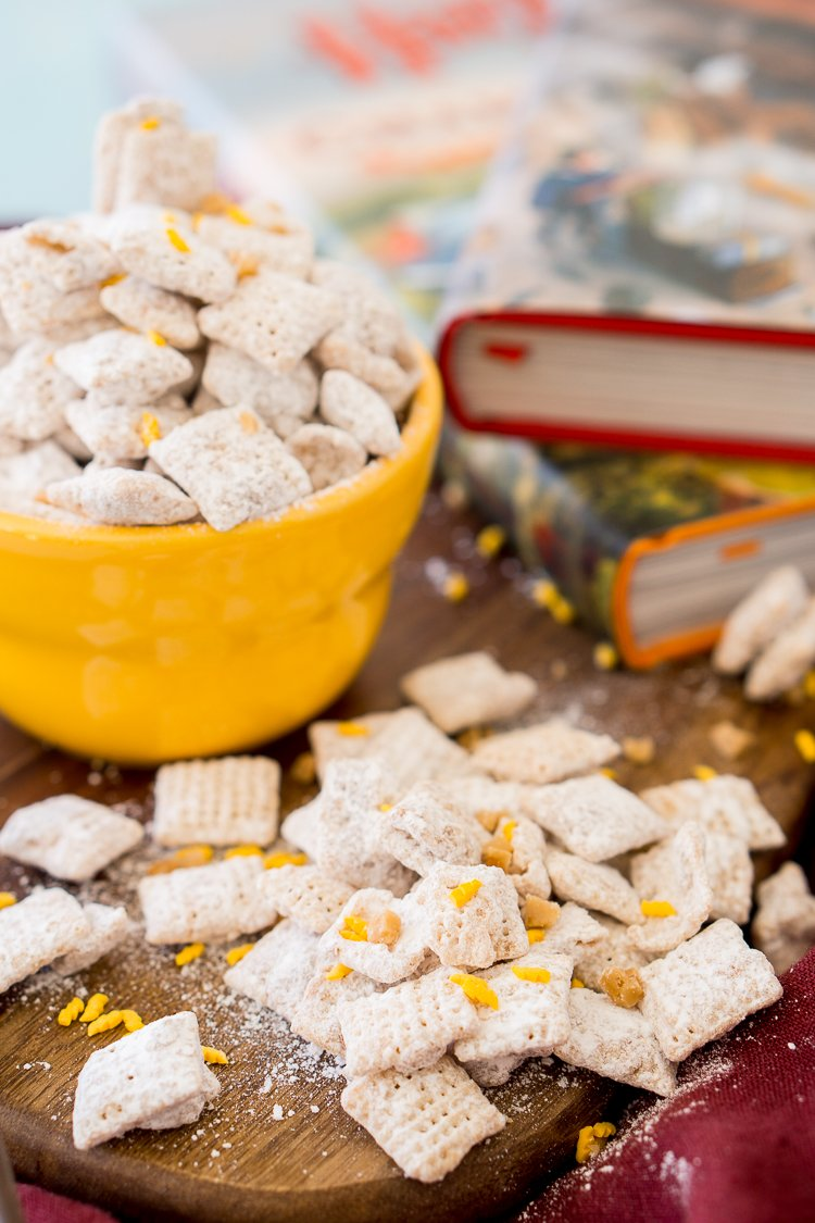 Butterbeer flavored muddy buddies scattered on a tables with a bowl behind them and Harry Potter books.