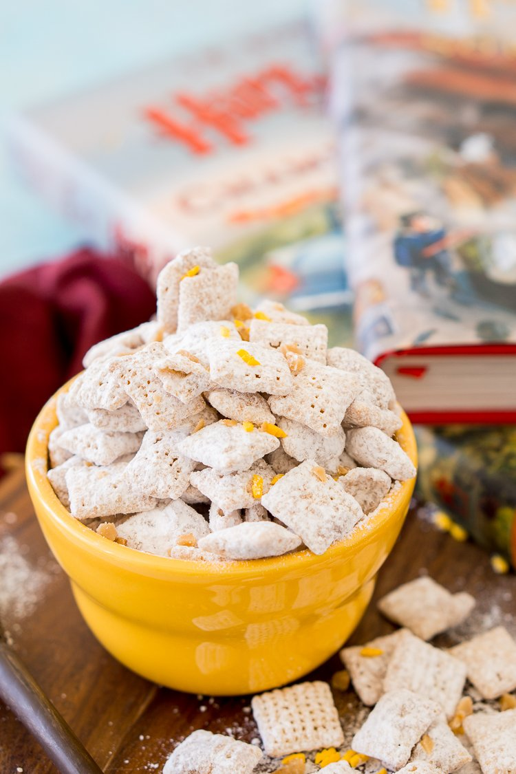 Butterbeer muddy buddies in a yellow bowl with Harry Potter books in the background.