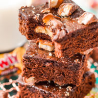Close up photo of a stack of three Twix Caramel Brownies with a bite taken out of the top brownie.