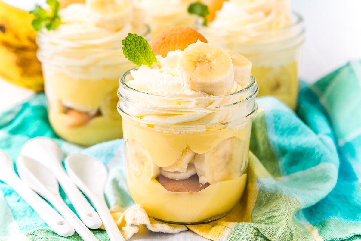Three mason jars filled with banana pudding on a blue napkin with white spoons to the side.