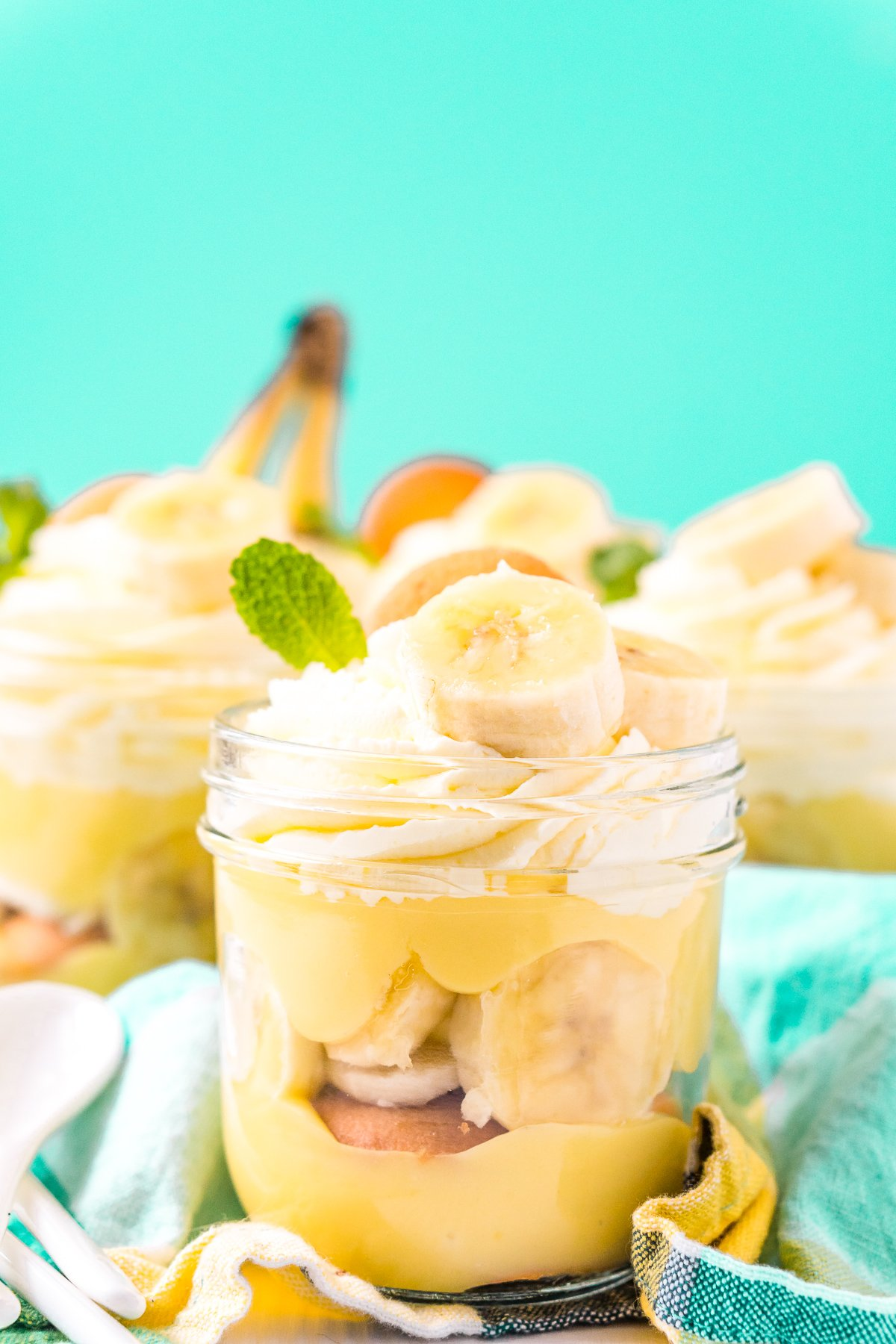 Jars of banana pudding on a blue napkin.