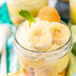 Small jar filled with banana pudding with banana slices, mint leaf, and nilla wafer on top.