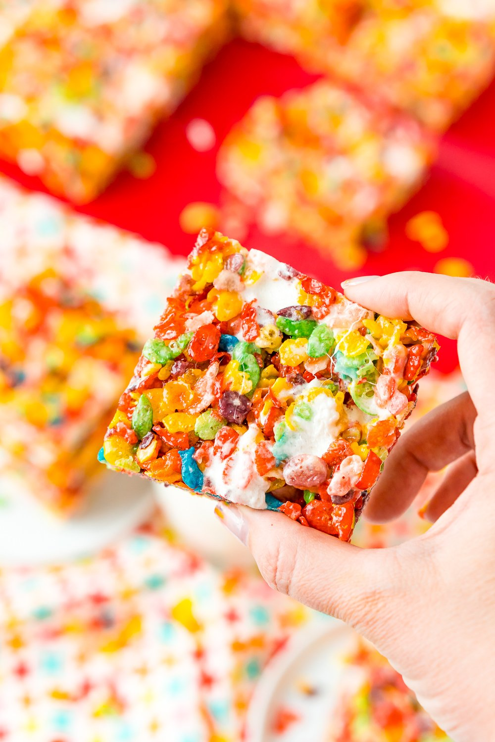 Woman's hand holding a fruity pebbles treat, more treats are in the background on a red cutting board.