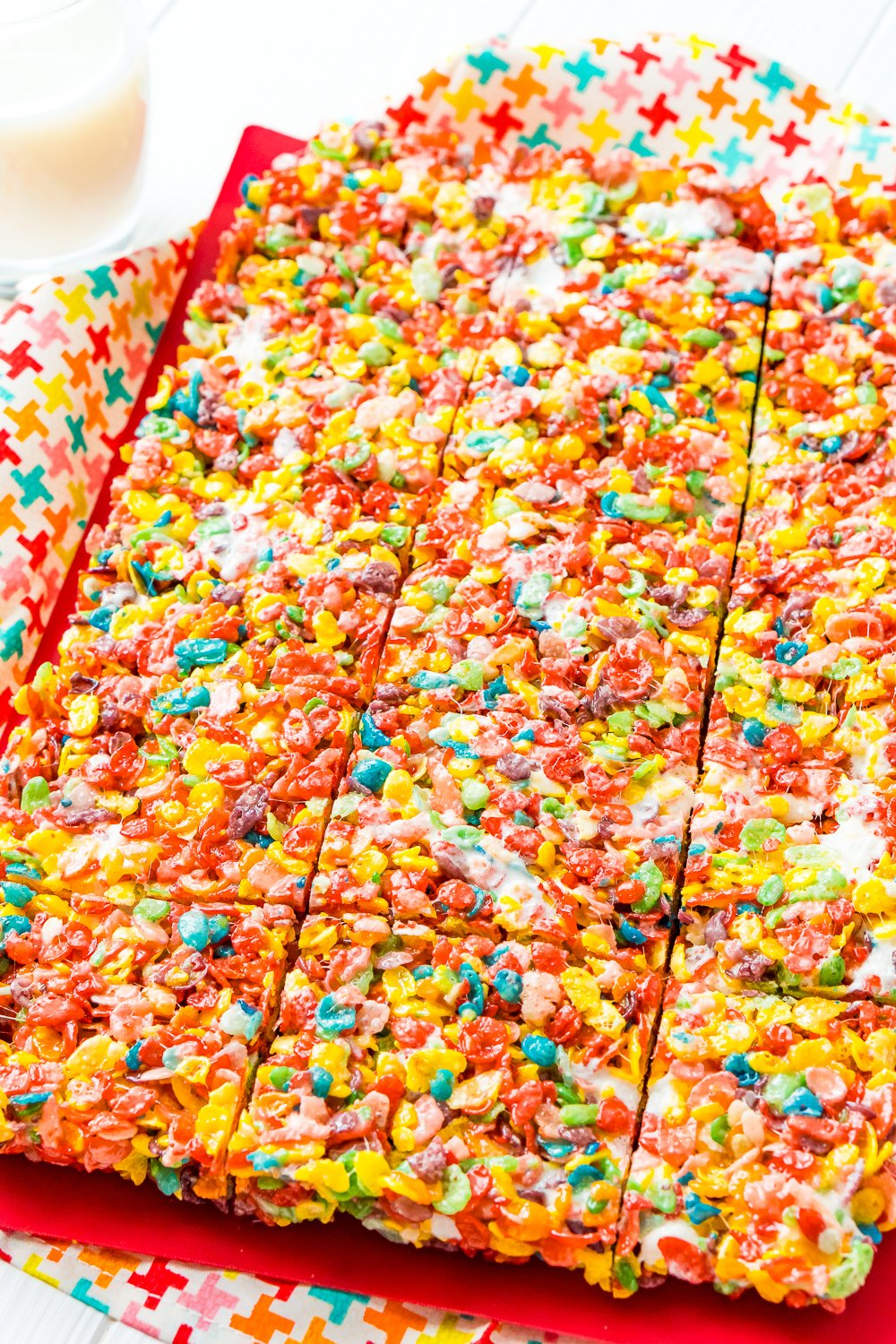 A sheet of fruity pebbles treats on a red cutting board. The treats have been cut but not pulled apart.