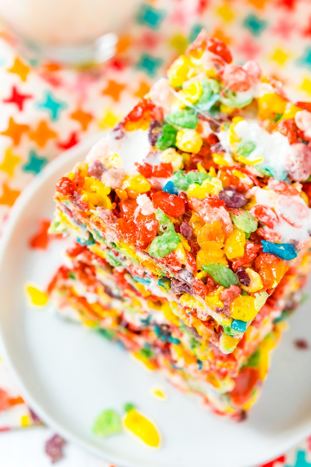 Stack of Fruity Pebbles Treats on a small white plate on a colorful napkin.