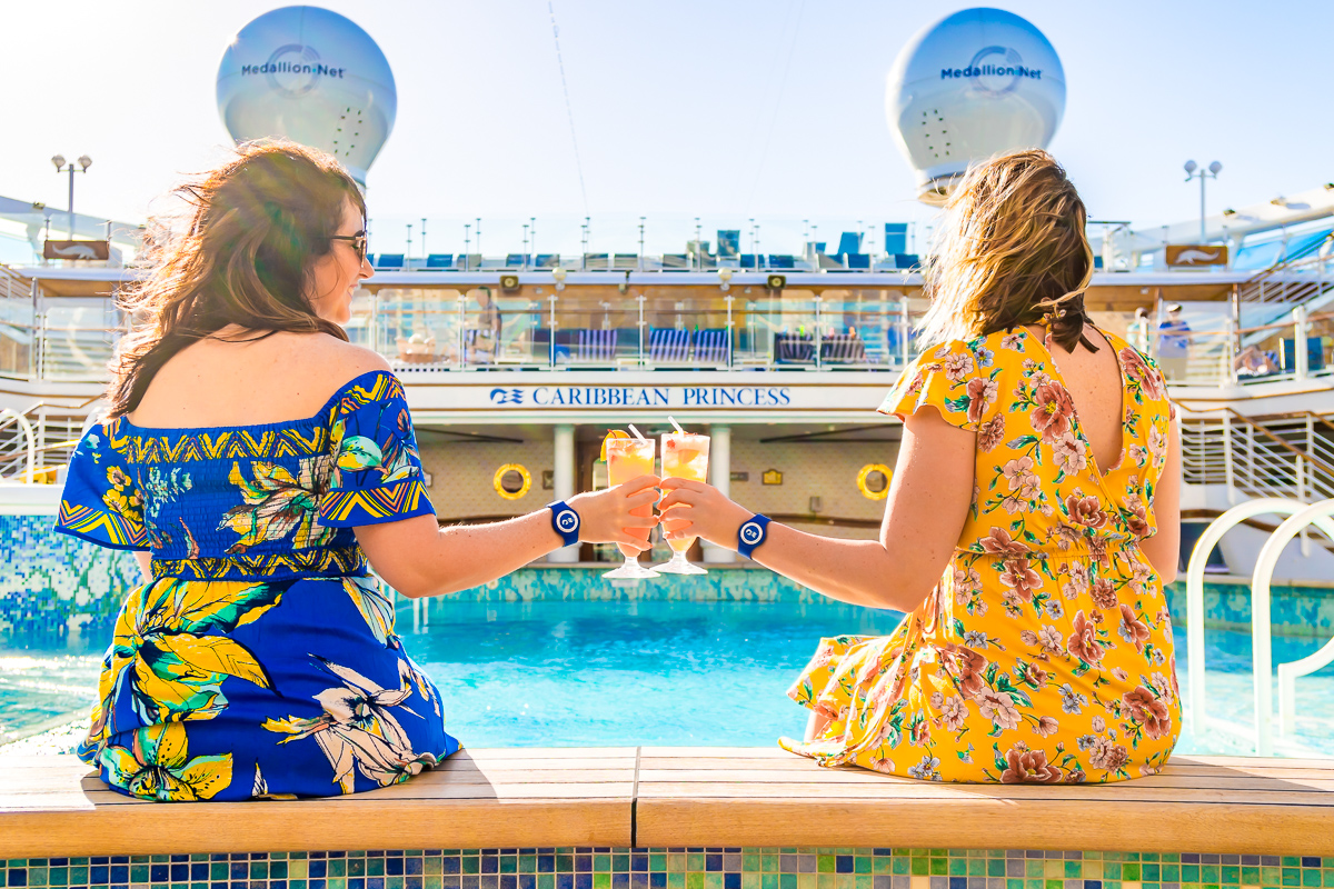 Two women cheers drinks sitting next to the pool on a cruise ship wearing floral dresses.