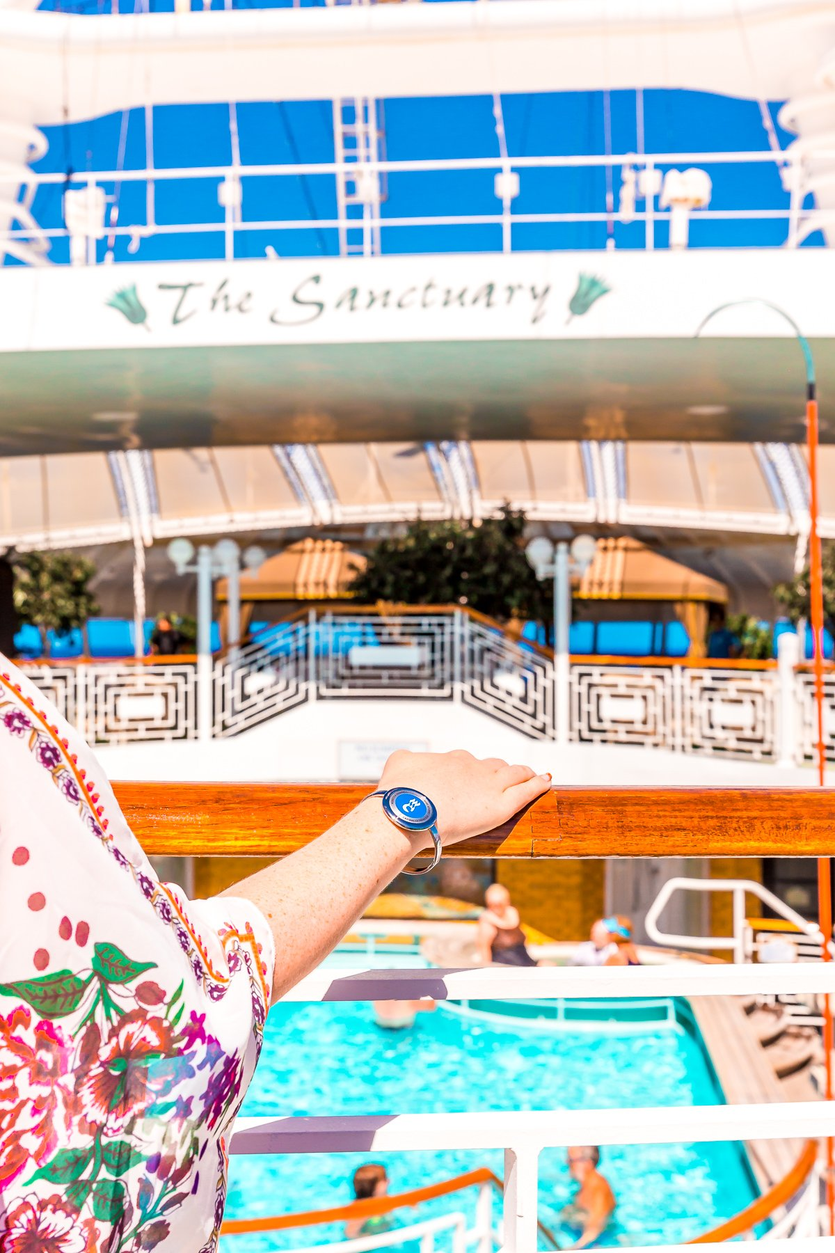 Woman's hand resting on a railing on a cruise ship.