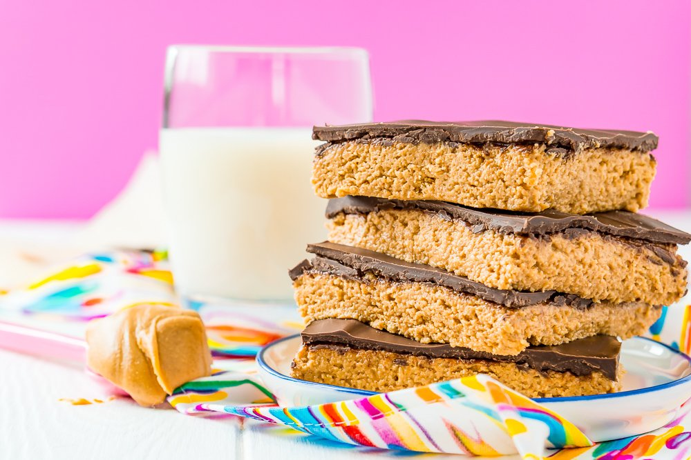Peanut butter bars stacked on top of each other on a small white plate with spoon of peanut butter next to it and glass of milk in the background.