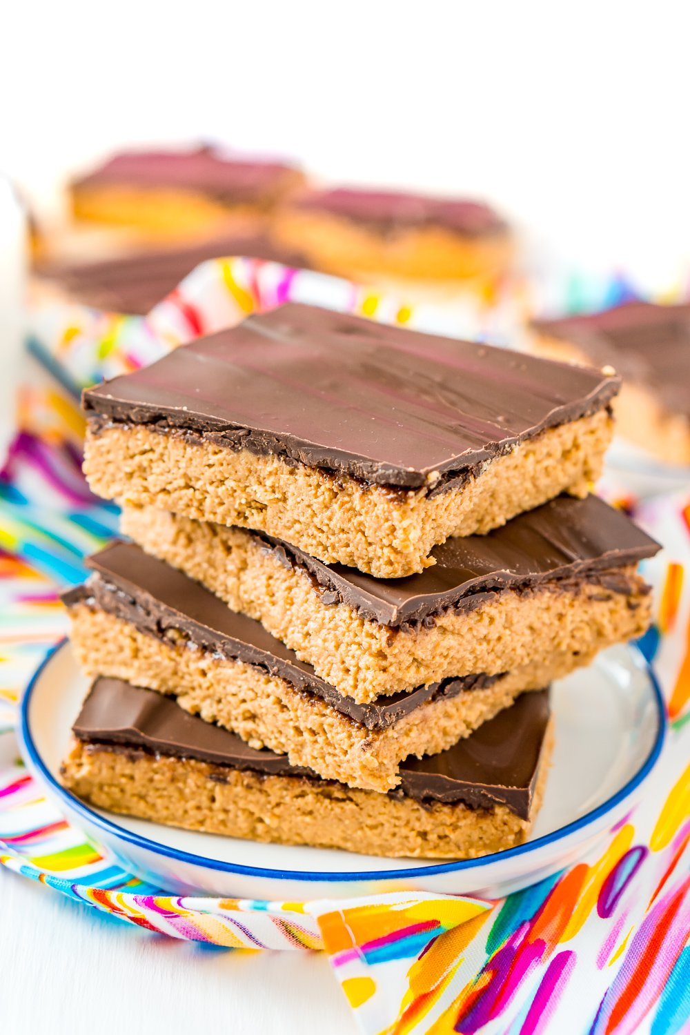 Stack of 4 peanut butter bars on a small white plate.