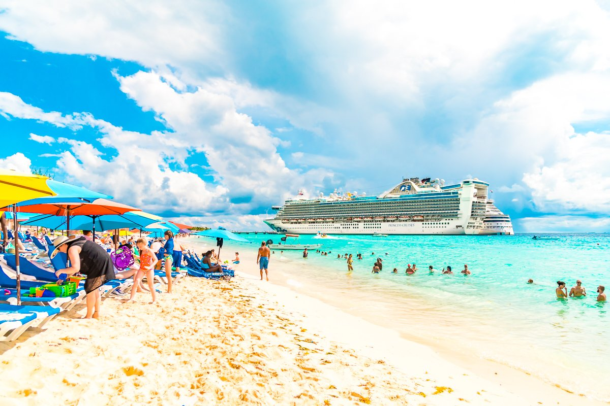 Caribbean Princess Cruise Ship in port in Grand Turk. Photo from the beach with people and colorful umbrellas.