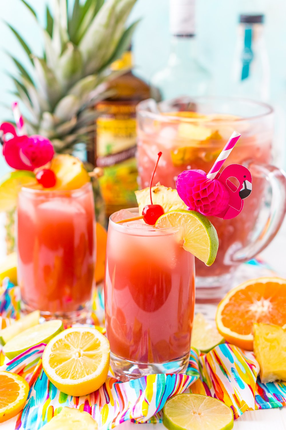 Glasses of rum punch with cherry, pineapple, and lime garnishes. Flamingo paper straws and a pitcher of punch in the background.
