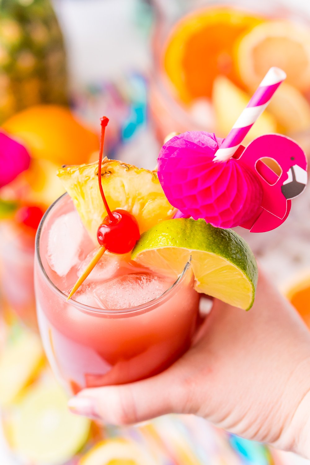 Woman's hand holding a glass of punch that's garnished with a cherry, lime wedge, and pineapple wedge and served with a flamingo paper straw.