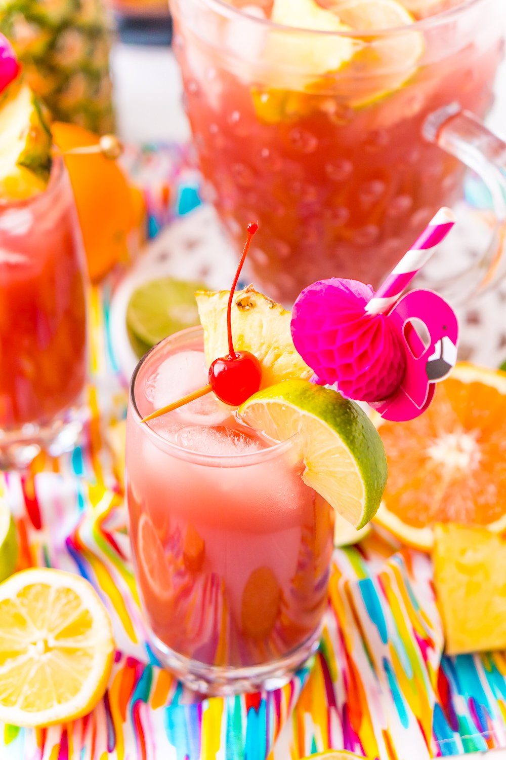 Glass of alcoholic punch garnished with cherry, lime, and pineapple and served with a flamingo straw. Fresh citrus slices scattered around the glass.