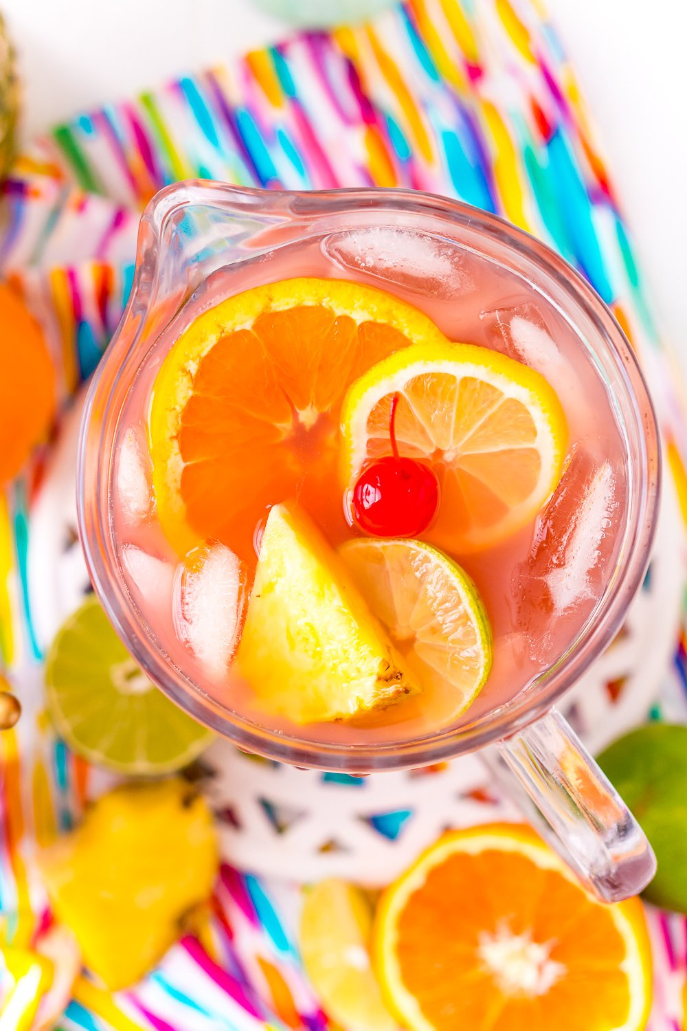 Pitcher of rum punch on a multi-colored napkin with fruit slices on the counter.
