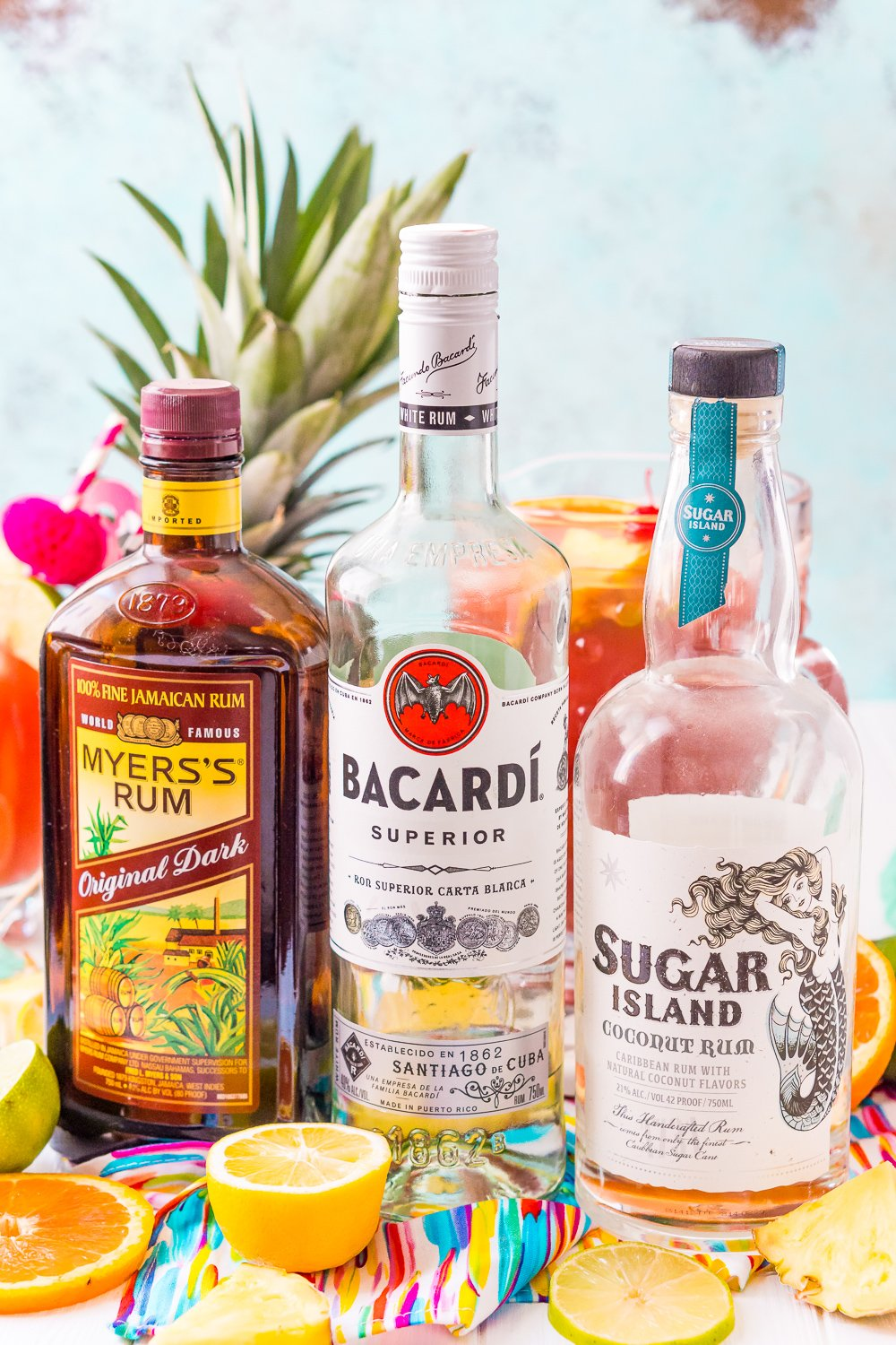 Bottles of Myer's Rum, Bacardi, and Sugar Island Rum lined up with a pitcher of rum punch and a pineapple in the background.