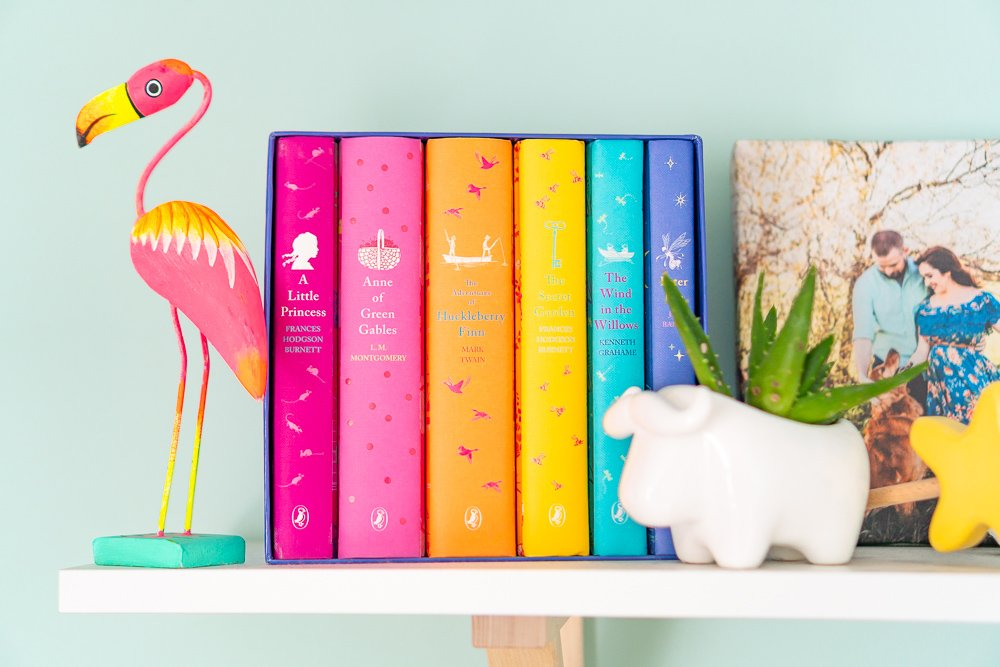 Rainbow books and plant holder on shelf in baby nursery