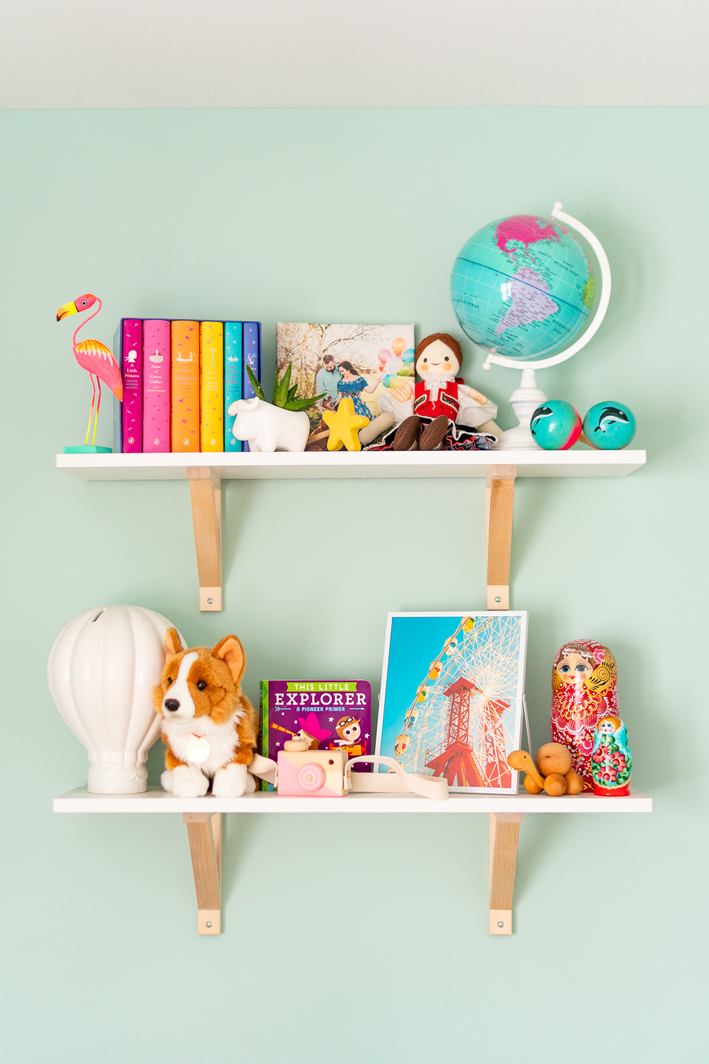 Travel inspired nursery decorations on shelves