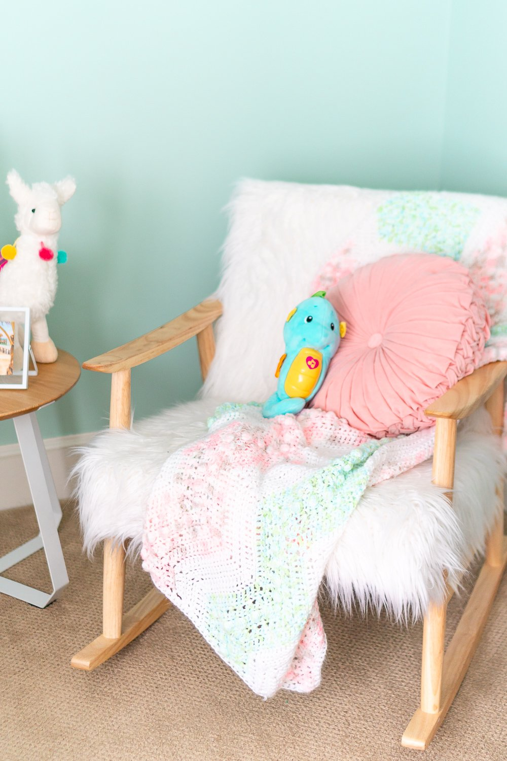 Faux Sheepskin and wooden rocking chair in a baby nursery with a knitted blanket and pink pillow on it.