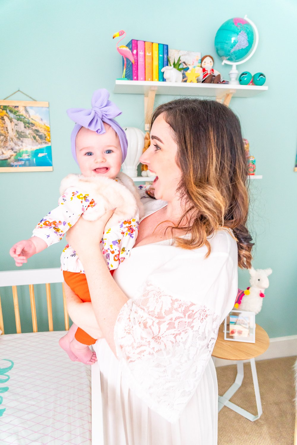 Mother and daughter standing by crib in travel inspired nursery.
