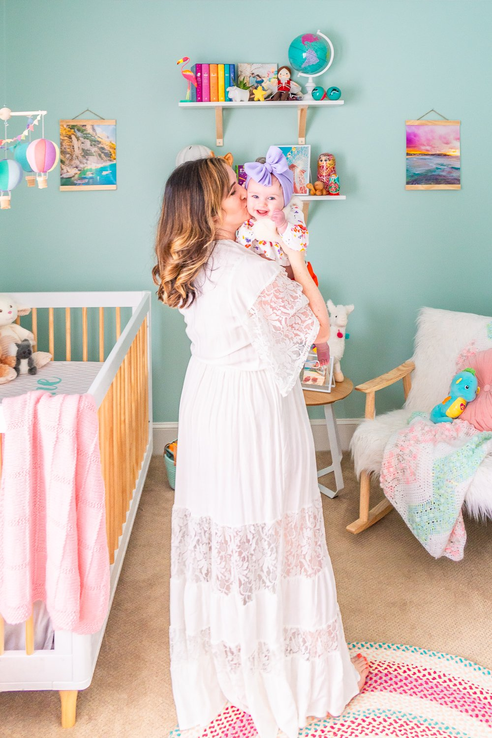 Woman holding baby girl in travel inspired nursery