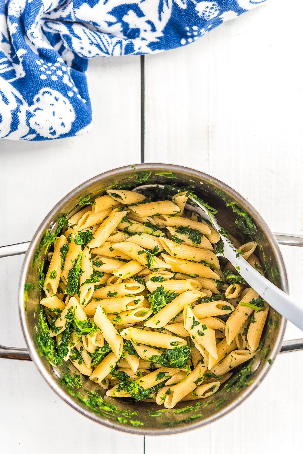 Cooked pasta in a pot with spinach on white wood table with blue and white napkin.