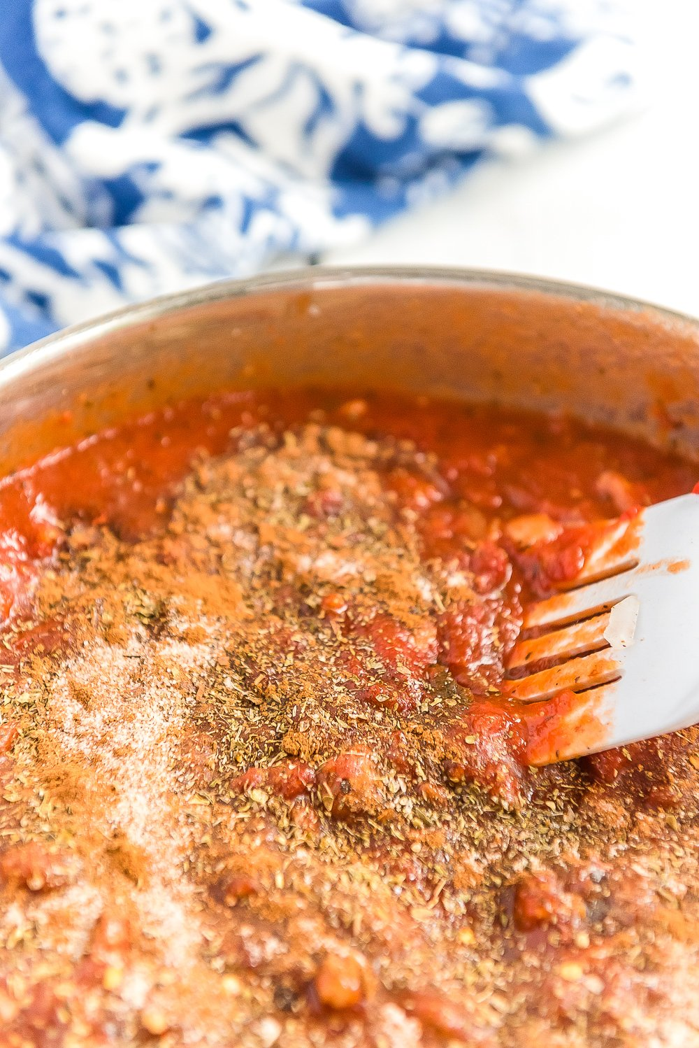 Red sauce with spices being simmered in a skillet.