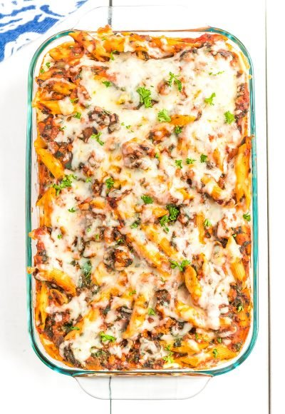 Casserole dish with turkey florentine pasta bake in it on white wood table.
