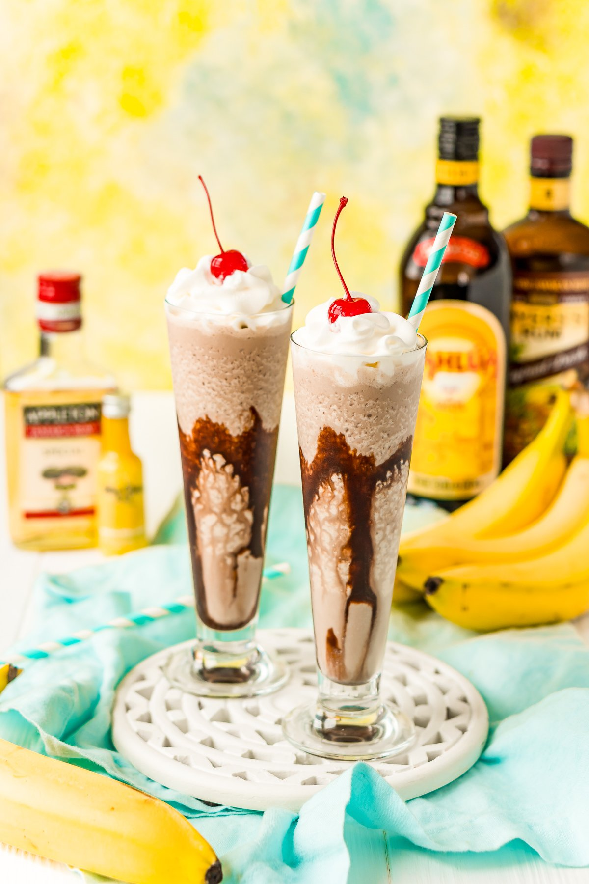Two dirty banana drinks on a white wooden board with bottles of rum and bananas in the background.