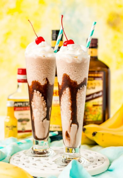 Frozen dirty banana drink in two glasses with bottles of rum and bananas in the background.