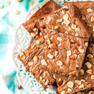 Brownies with chopped hazelnuts on a white plate with a blue and white napkin.