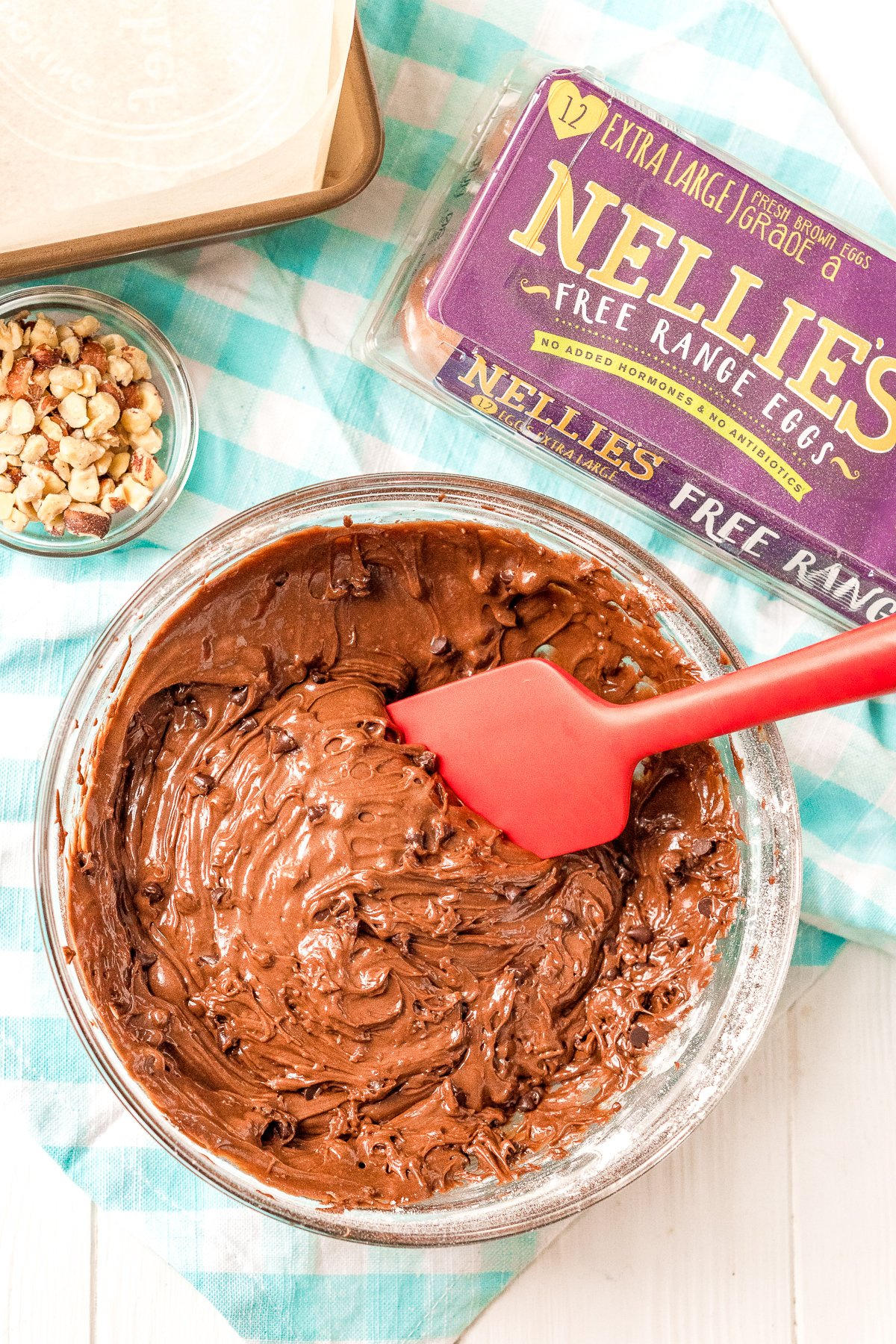 Brownie batter in a large mixing bowl with a smaller bowl of chopped hazelnuts next to it.