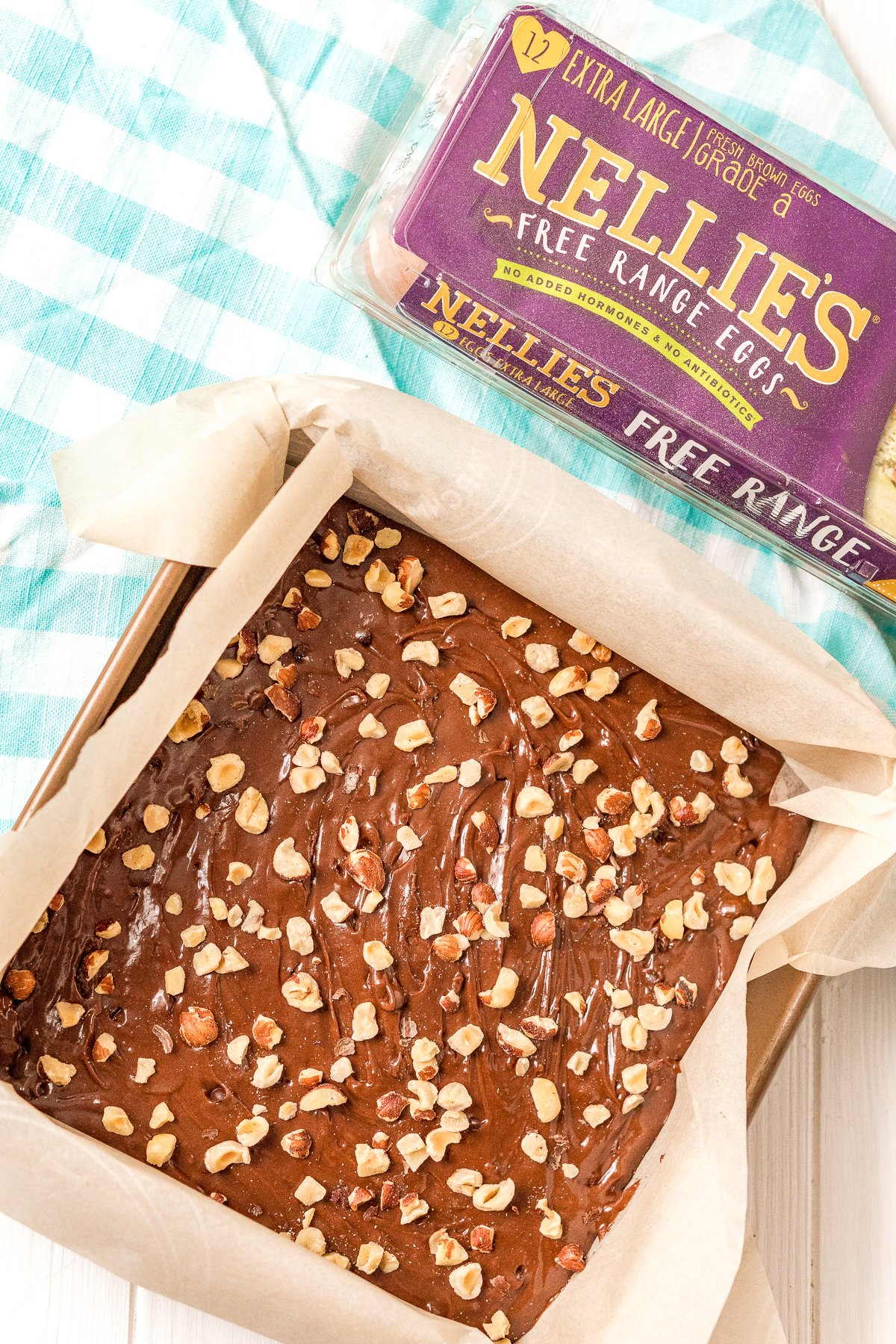 Uncooked brownie batter in a square baking dish topped with chopped hazelnuts next to a carton of eggs.