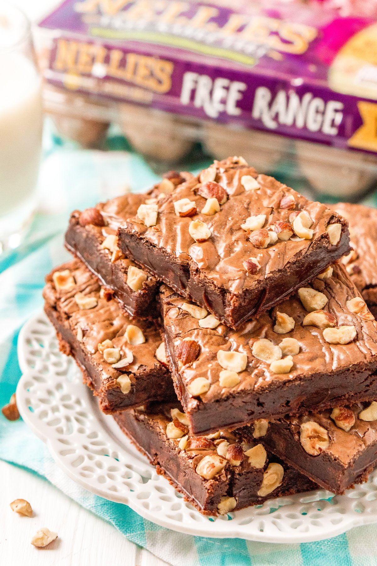 Brownies with hazelnuts stacked on a white plate with a carton of eggs in the background.