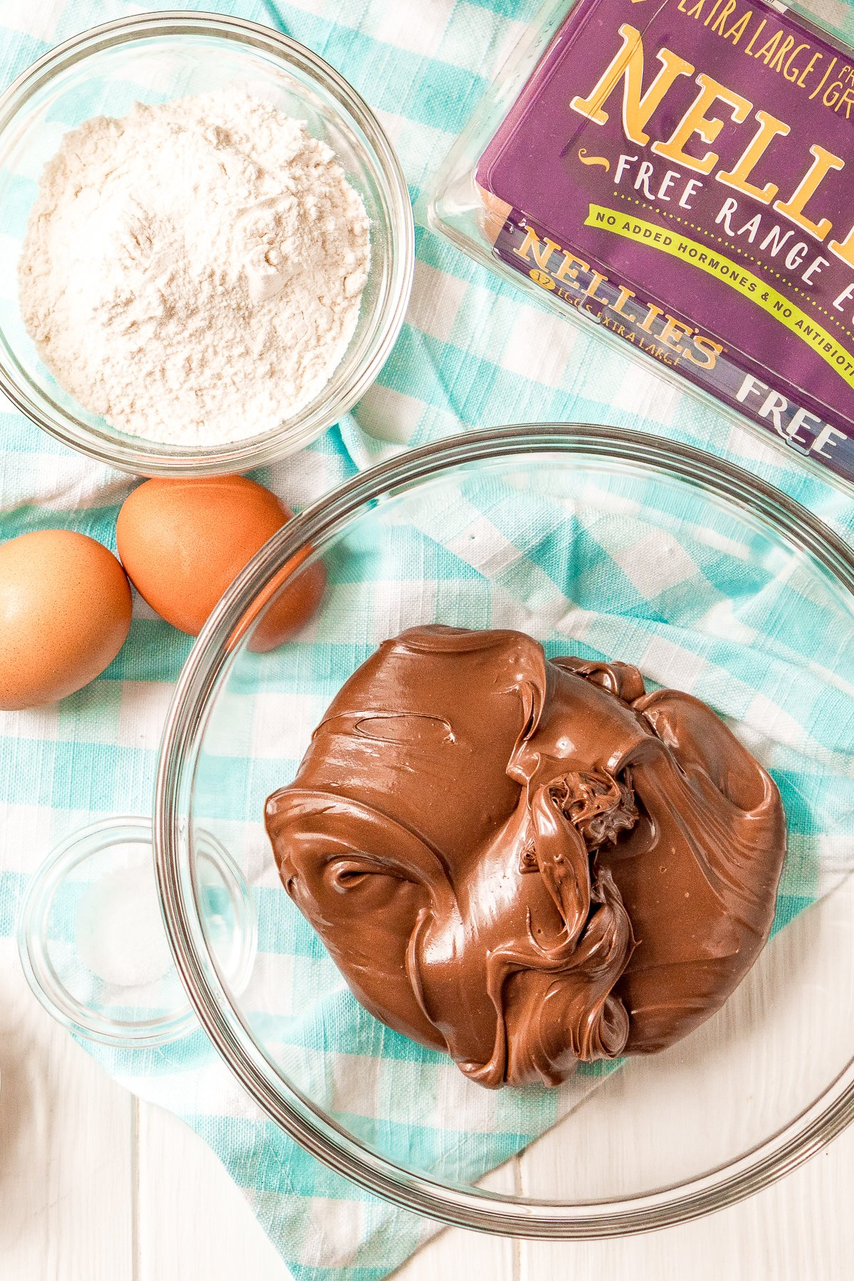 Nutella in a glass bowl with carton of eggs, loose eggs, small bowl of flour and salt on a white and blue napkin.