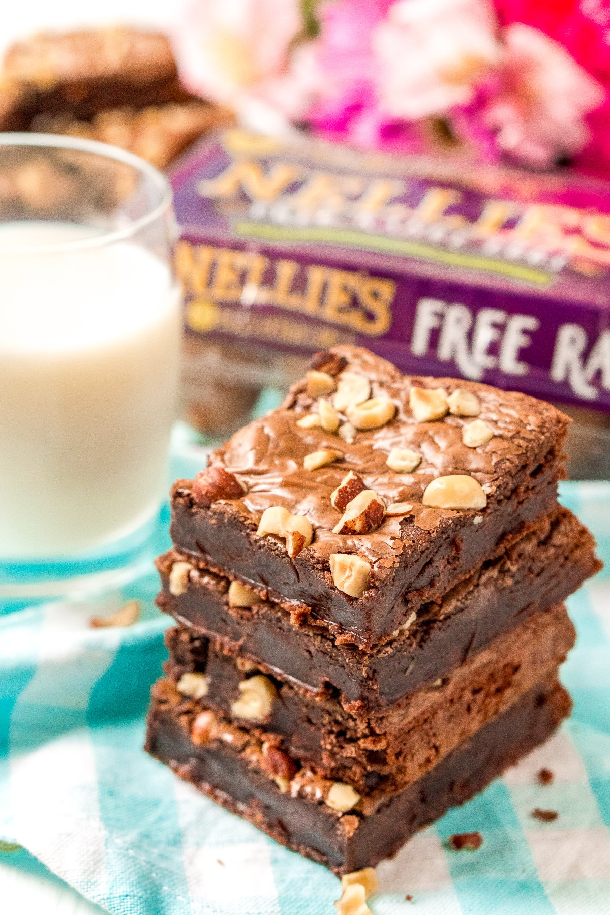 Stack of hazelnut brownies with a glass of milk in the background.
