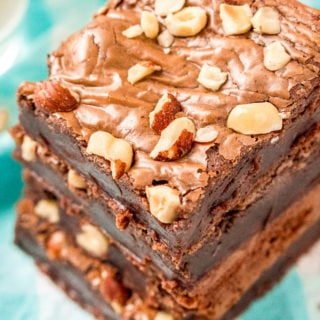 Overhead angled photo of a stack of hazelnut brownies with hazelnuts on top on a blue and white napkin.