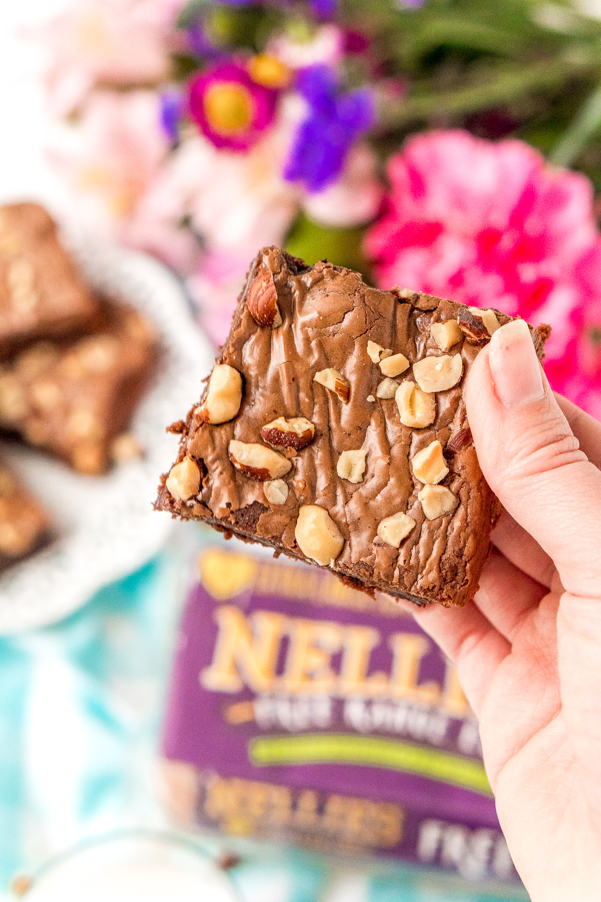 Woman's hand holding a hazelnut brownie. More brownies and flowers in the background.