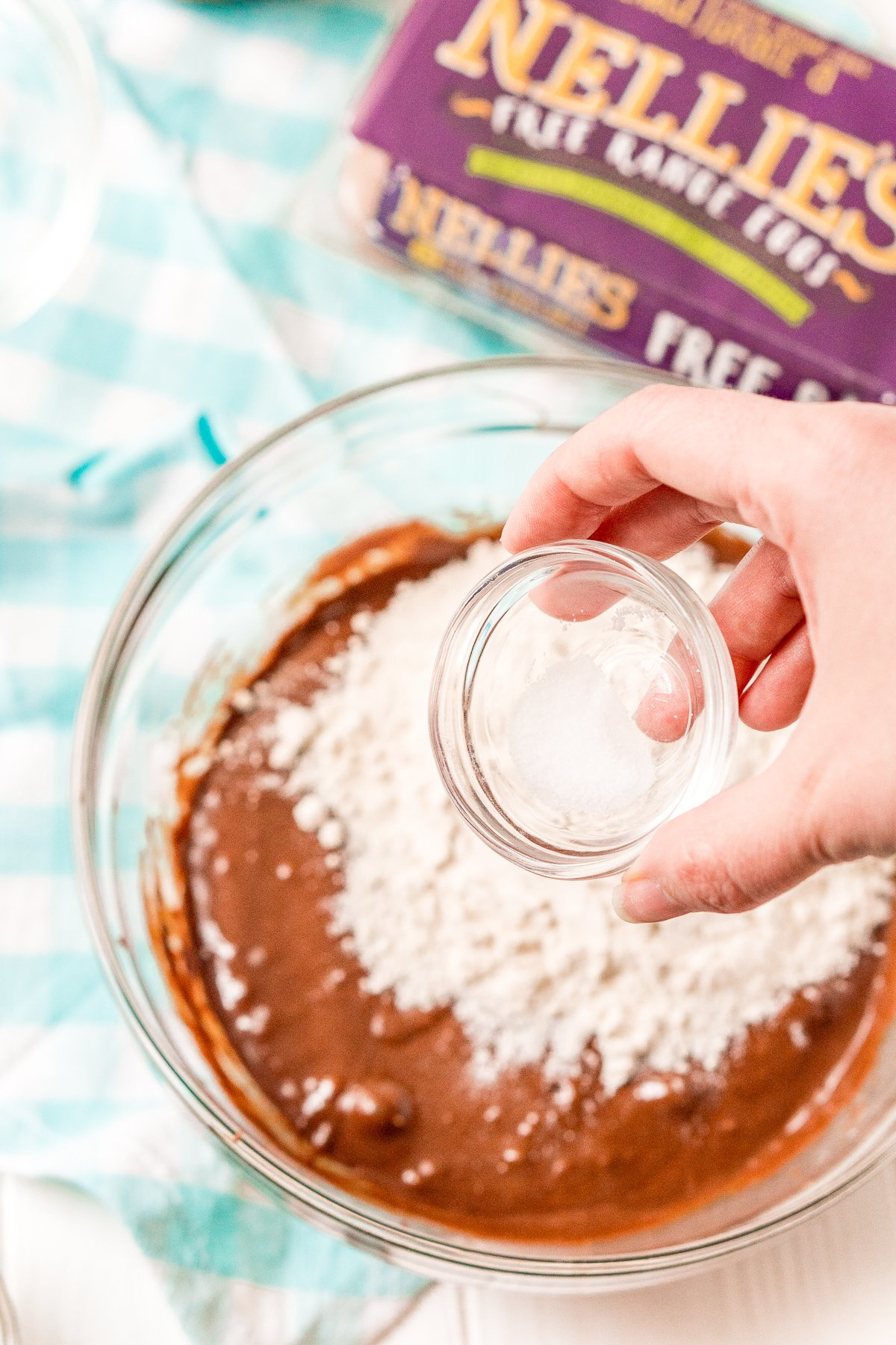 Salt being added to a bowl of brownie mix and flour.