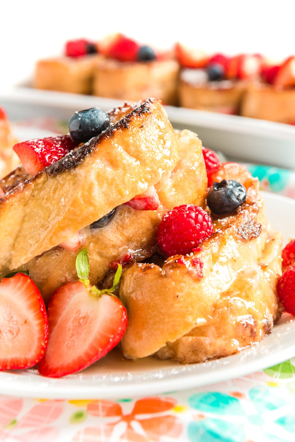 Berry French Toast on a white plate with more slices of french toast on a plate in the background.