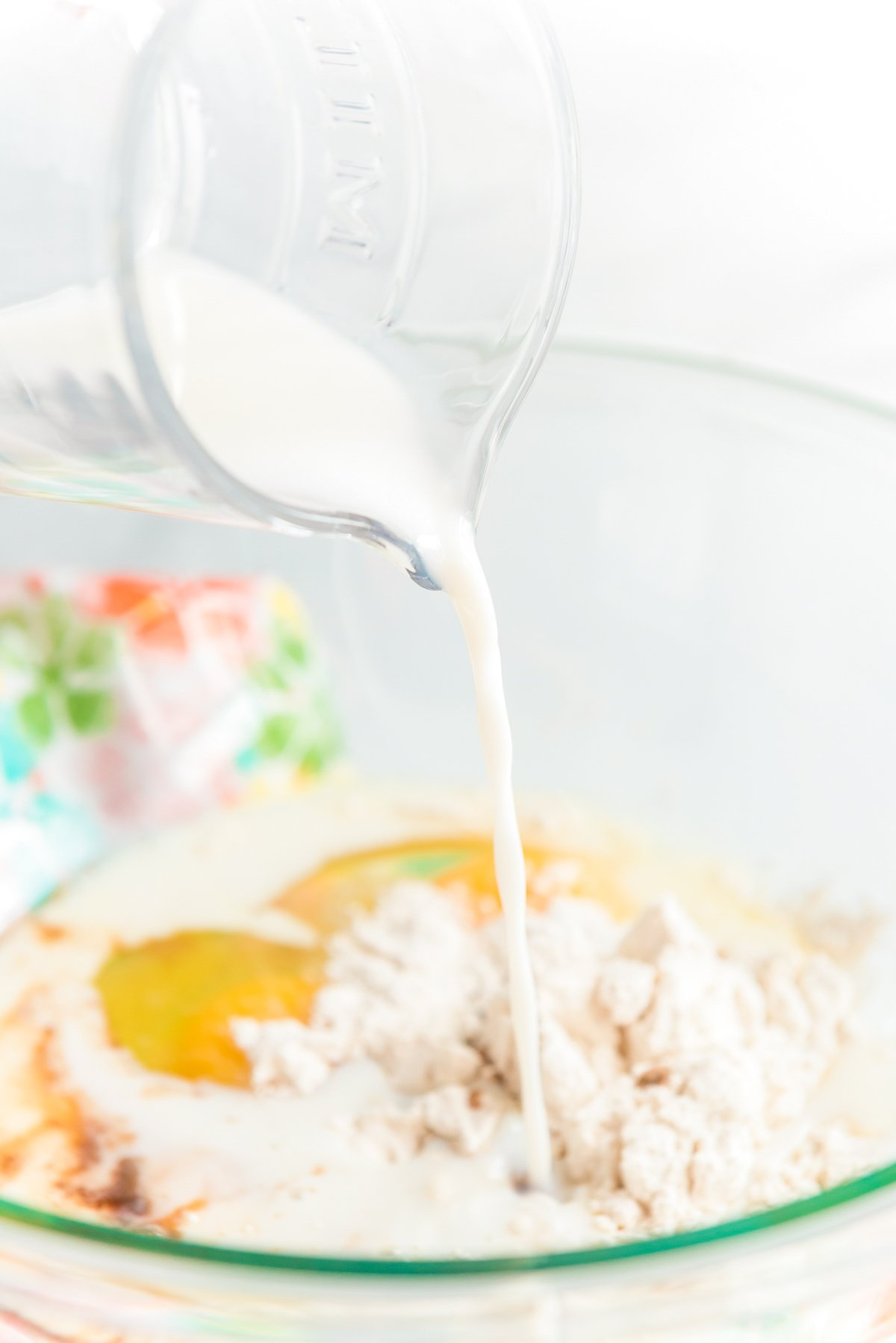 Milk being poured into a mixing bowl with eggs and flour.