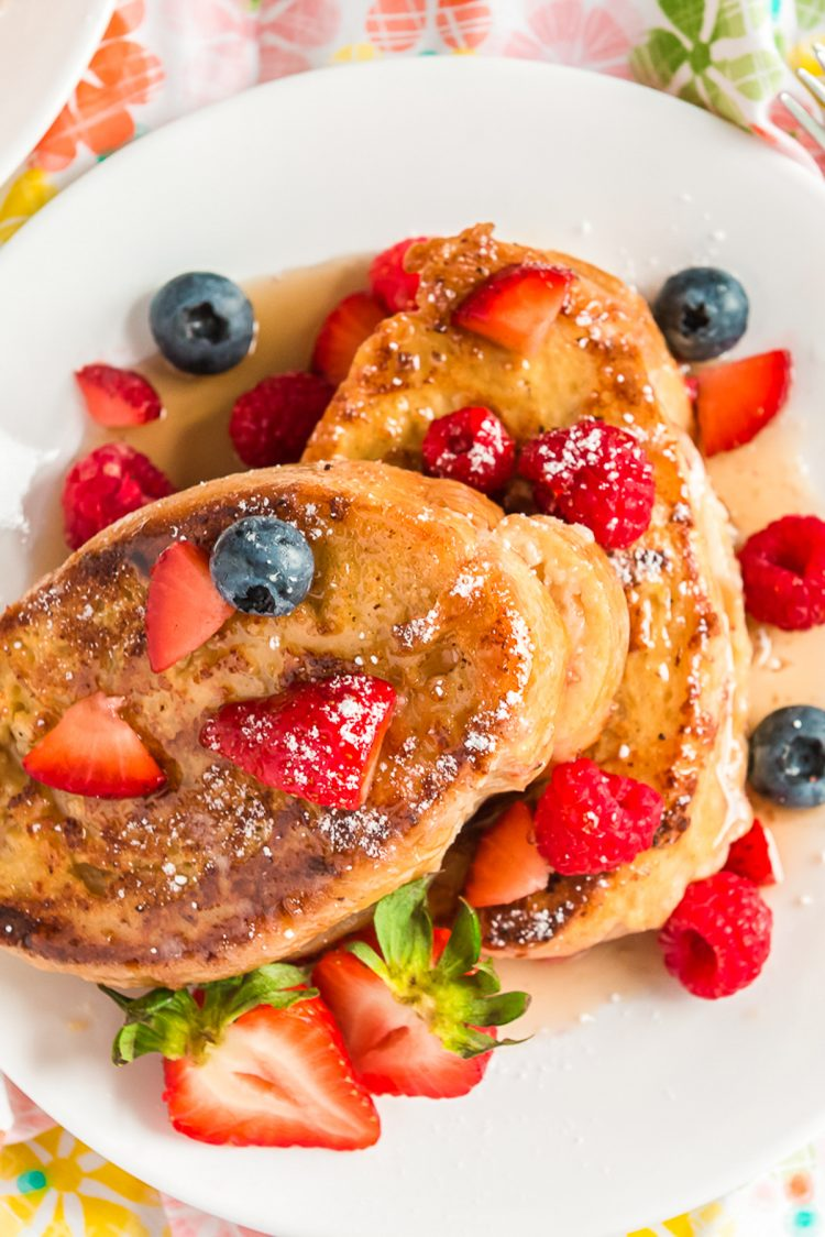 Overhead photo of French toast topped with berries and maple syrup on a white plate.