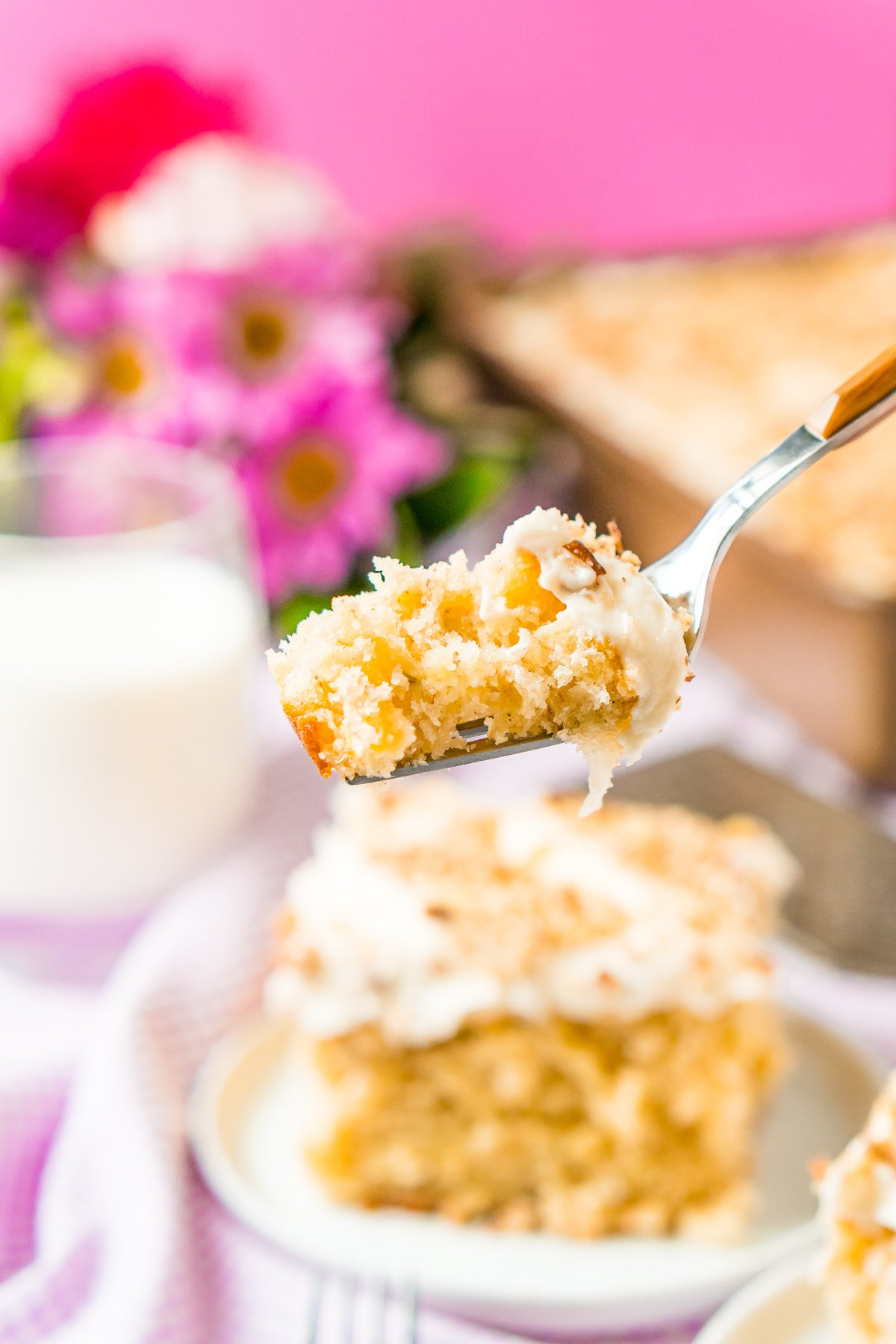 Close up photo of a fork with a bite of hummingbird cake on it.