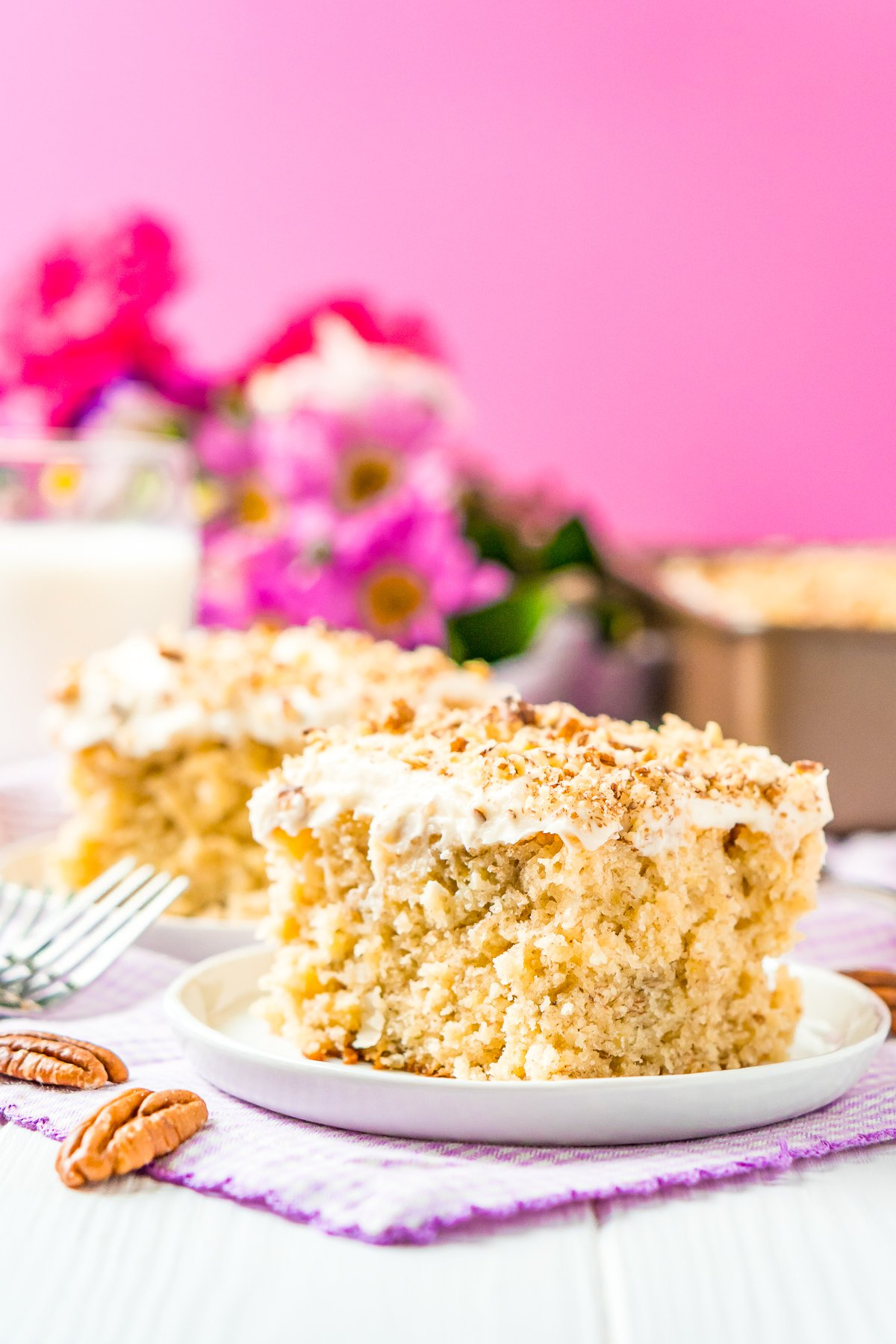 Two slices of hummingbird cake on small white dessert plates with a pink background.