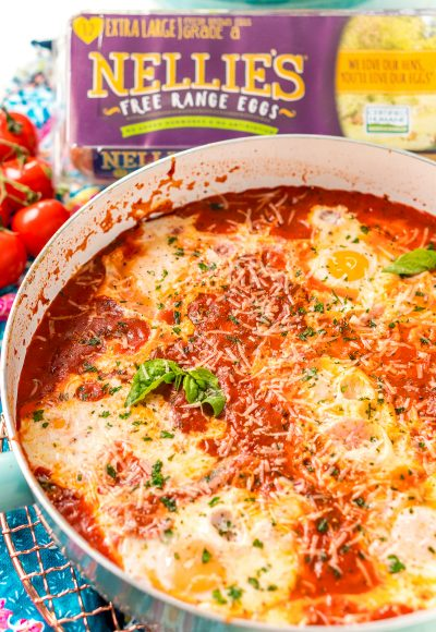 Italian Eggs In Purgatory in a skillet with cherry tomatoes and a carton of eggs in the background.