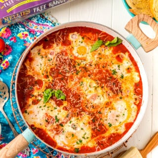 Overhead photo of Eggs In Purgatory in a skillet with additional ingredients scattered around it.