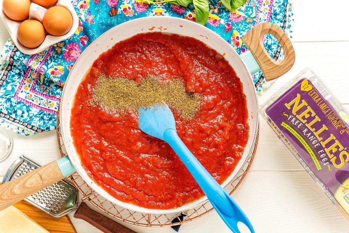 Italian Seasoning being added to a fry pan with tomato sauce.