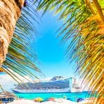 Photo of a Princess Cruise Ship in port. Palm trees bordering the photo in the foreground. Beach umbrellas.