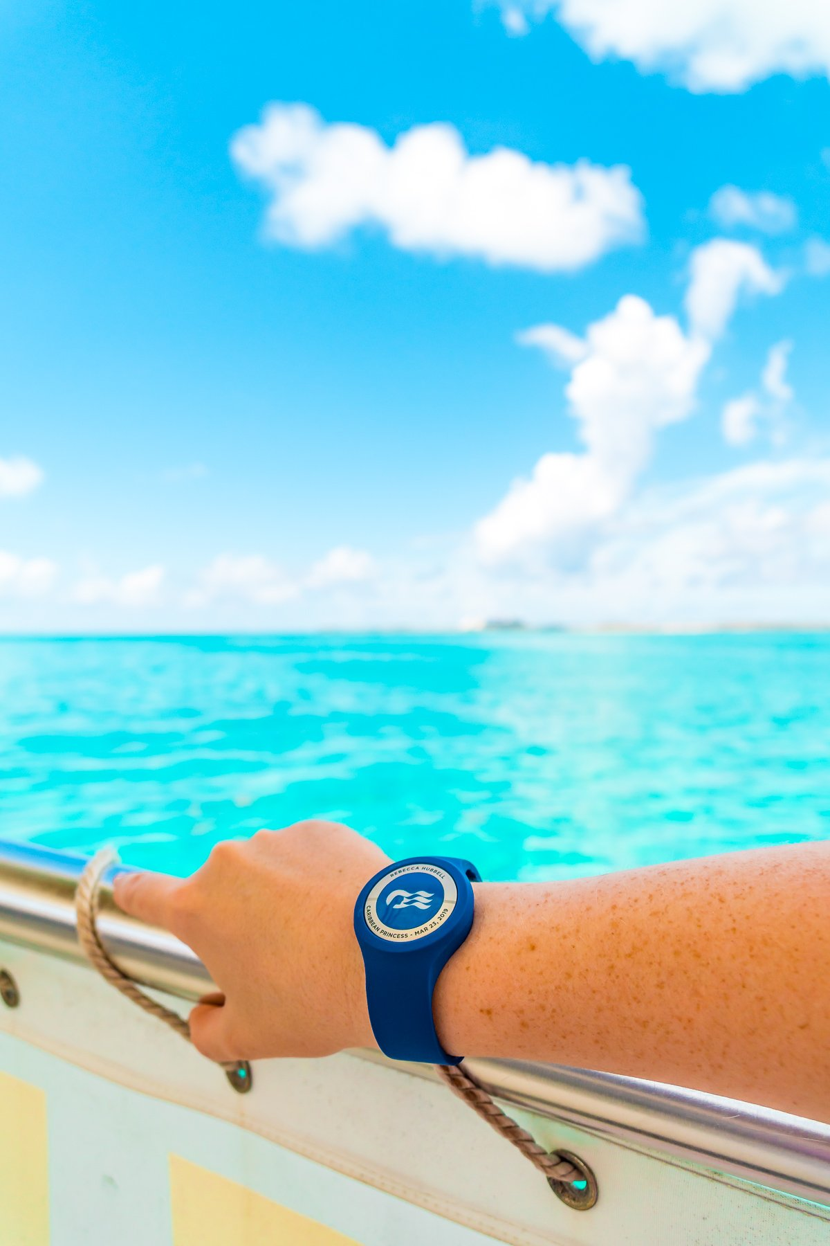 Princess Cruises Ocean Medallion watch on a woman's arm on a boat overlooking the Caribbean.