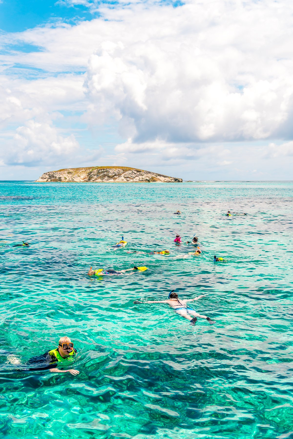 People snorkeling in the clear turquoise waters of Grand Turk in the Caribbean.